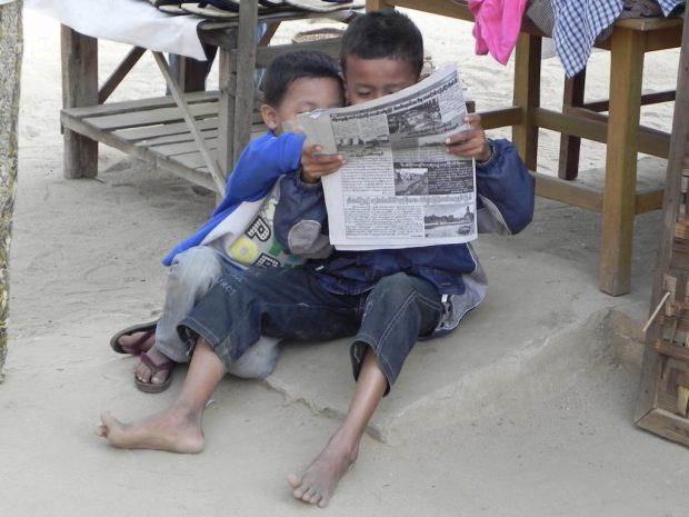 lesende Kinder auf einem Markt in Myanmar
